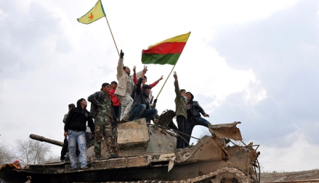 Civilians and members of the YPG gesture and raise flags atop a tank that belonged to fighters from the ISIL, in al-Manajeer village of Ras al-Ain countryside