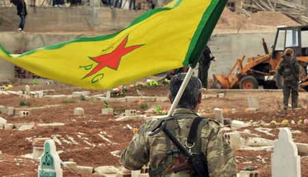 A Kurdish fighter from the Popular Protection Units (YPG) carries his party's flag at the 'Martyrs' Cemetery' in the town of Derbassiye in northeast Syria